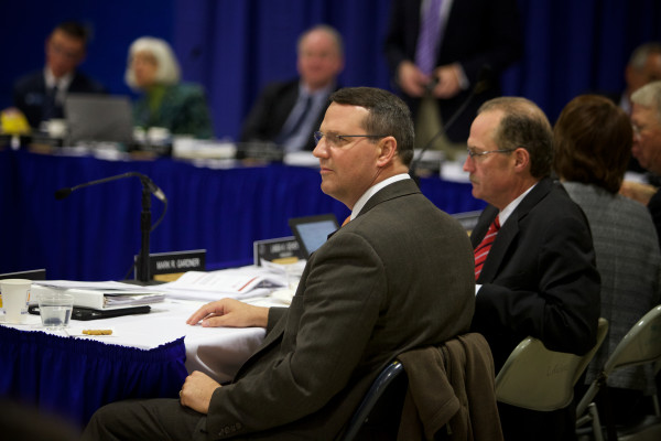 University of Maine System trustees watch as chanting protesters interrupt their meeting on Monday in Portland.