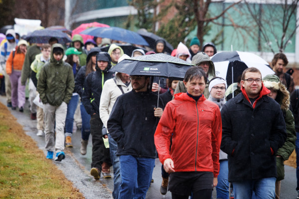 Protesters demanding an end to recent cuts march through the rain to Sullivan Gym on the USM campus on Monday in Portland.