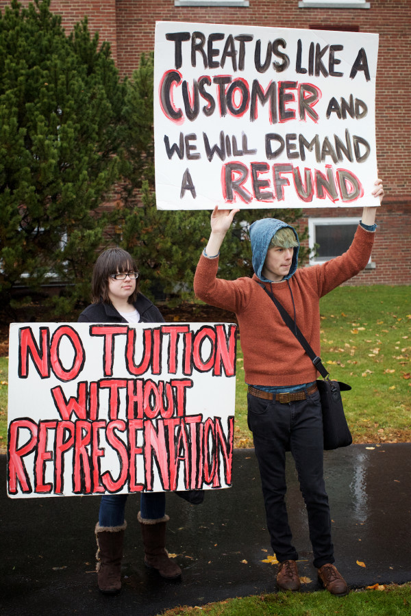 University of Southern Maine art students Shannon Sockalexis (left) and Chris Armstrong protest program and faculty cuts at a student walk-out on Monday in Portland.