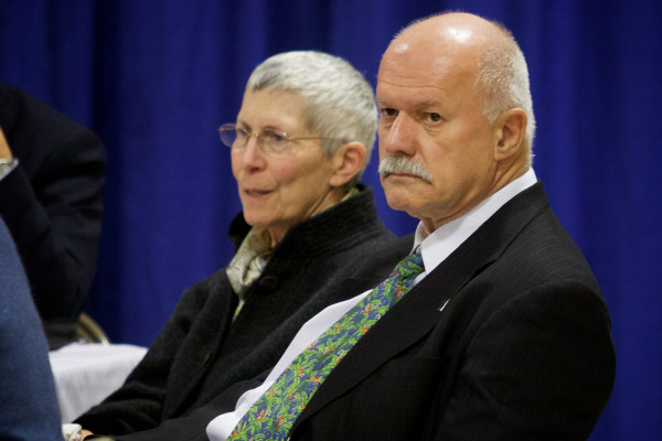 University of Southern Maine President David Flanagan (right) and Theo Kalikow, former president, watch as protesters demonstrating against faculty and program cuts interrupt and briefly take over a meeting of University of Maine System trustees on Monday in Portland.