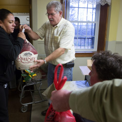 Manna Ministries' Bill Rae (center) hands Tania Perry a free turkey Wednesday morning at the ministries in Bangor.