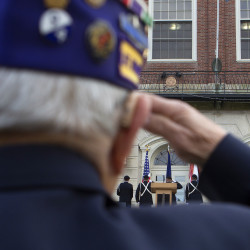 Noram Rossignol, Army Infantry, salutes the flags as the University of Maine presents arms during a ceremony honoring veterans on Monday outside University of Maine's Fogler Library in Orono.