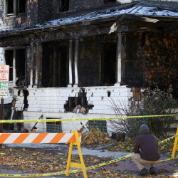 A man stoops and gazes at the remains of 20 Noyes St. in Portland on Monday. Five people died at a fire at the house on Saturday. Steven Summers died at Massachusetts General Hospital where he was being treated for injuries sustained in the fire.