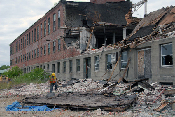 Tom Pelkey of Eddington, an equipment operator with J.E. Butler LLC of Holden, helps gather recyclable debris at the former Howland tannery building on July 26, 2012.