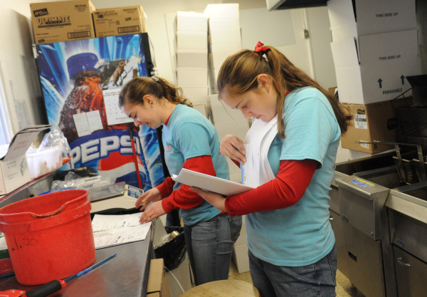 Katie (left) and Mikayla McLaughlin look through order forms before packaging up orders of live lobsters at McLaughlin Seafood in Bangor to be overnight shipped to customers around the country. They are sending over 100 boxes containing more than 300 live lobsters and 100 cooked lobsters.