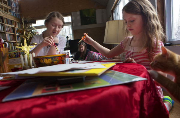 Asha Kirkland (left), 13, and her sister Aria Tapman, 6, paint holiday cards in their Itty Bitty House while their mother, Jennifer Jacques, sits on the couch in Orland on Saturday.