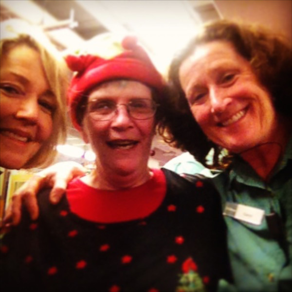BDN writer Kathleen Pierce takes a picture with staff members at the holiday party, including Diane Markowski (left) and Carol Minnehan.