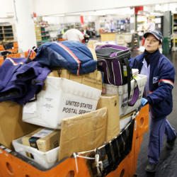 "Jen Bailey, a 20-year veteran of the U.S. Postal Service, wheels her ""hamper"" of letters and packages out of the sorting facility deep beneath the post office on Forest Avenue in Portland on Thursday -- the busiest day of the year."