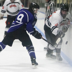 Brewer's Caleb Eggert (right) and Waterville's Dalton Henderson try to gain control of the puck during their hockey game on Wednesday at Penobscot Ice Arena in Brewer.
