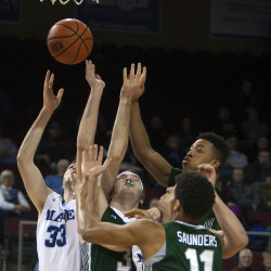 University of Maine's Ethan Mackey (left) battles for a rebound with Wagner players during their basketball game Tuesday at Cross Insurance Center in Bangor.