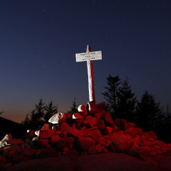 "The summit marker atop 768-foot-tall South Bubble mountain is lit by an off-camera flash, and the rocks at its base are ""painted"" with a red-filtered headlamp in a 30-second exposure made at dusk in Acadia National Park."
