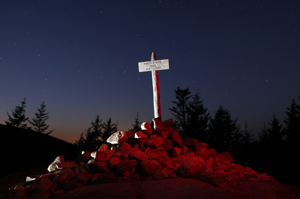 The summit marker atop 768-foot-tall South Bubble mountain is lit by an off-camera flash, and the rocks at its base are &quotpainted&quot with a red-filtered headlamp in a 30-second exposure made at dusk in Acadia National Park.