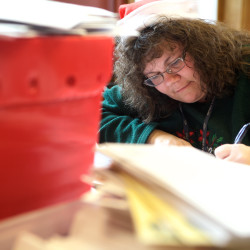 Donna Martin helps answer letters to Santa at the Forest Avenue Post Office in Portland on Monday. This year, volunteers will answer about 800 letters.