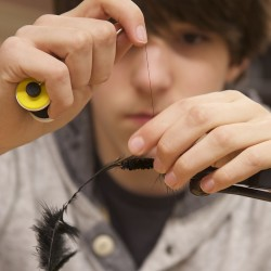 Brian Brown, a Brewer High School student, ties a black woolly booger Thursday morning in the school's lecture hall. Brown's grandfather was a fly fisherman and he hopes to take up the sport. Student's received lessons from the Penobscot Fly Fishers as part of their outdoors education class.
