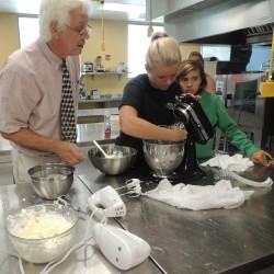 A student makes butter with professor Joseph Kakareka