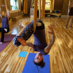 Holly Twining (center), twists her body while using the aerial yoga hammock while  Christine Mihan (left) and Terry Lacy stretch at Om Land Yoga in Brewer Tuesday. Om Land Yoga is the only place in Maine to offer aerial yoga on a regular basis.