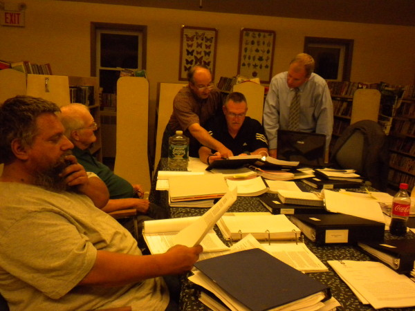 Clifton Planning Board member Gerald Foster (left) reviews some of the 8,000 pages of documents that pertain to the board's review of the permitted Pisgah Mountain wind farm on Aug. 14, 2013, with Vernon Campbell beside him. Planner Bruce Jellison (standing left) points out a section of the land use ordinance to Chairman Eric Johns (seated center) with David Szewczyk, the town's attorney, looking on.