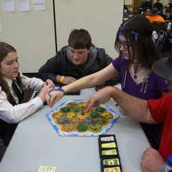Miranda Stevens (second from right), makes her next move in Settlers of Catan while Matthew Hoelzer (from left), 13, Garreth Alley, 14, Jonathan Landers, 14, and Nikky Boyington (right) watch during the seventh annual SnowCon at the Cross Insurance Center in Bangor on Saturday. The two-day event allowed board game enthusiasts to play their favorite games, along with learn the rules of new games.