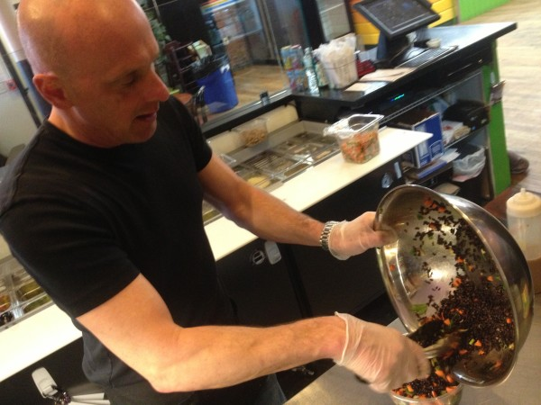 Daily Greens owner John Conzelman makes the Emperor, a chicken salad served on warm black rice.