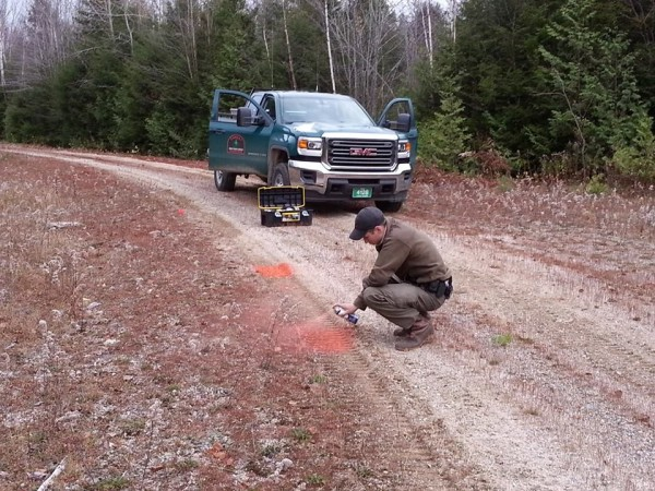 A Maine Forest Ranger collects evidence on a property abuse case in October 2014. The case involved criminal trespass, damaging forest land with a motor vehicle and littering. A summons was issued, according to rangers.