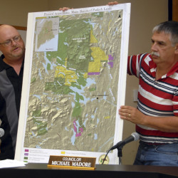 Millinocket Town Councilor John Raymond [left], explains a map with assistance from Councilor Michael Madore during a Town Council meeting August 2011.