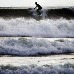 Reed McDermott rides a wave on Wednesday at Higgins Beach in Scarborough. A day after a blizzard brought snow to Maine, the waves were 2 to 4 feet high, according to magicseaweed.com.