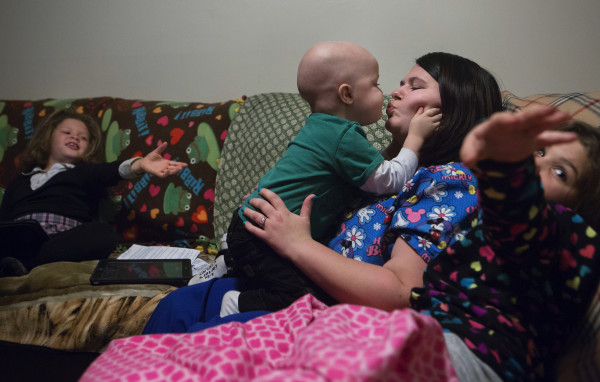 Tripp Murray (center), 3, gives his mother a kiss while his two sisters watch at their home in Bangor on Thursday. Tripp is currently in remission for brain cancer. Last year, he had a brain tumor removed and also underwent a bone marrow transplant.