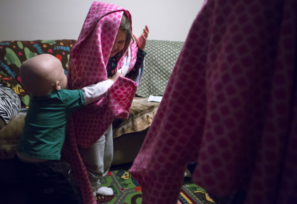 Tripp Murray, 3, covers his sister with a blanket in their home in Bangor on Thursday. Tripp is currently in remission for brain cancer. Last year, he had a brain tumor removed and also underwent a bone marrow transplant.