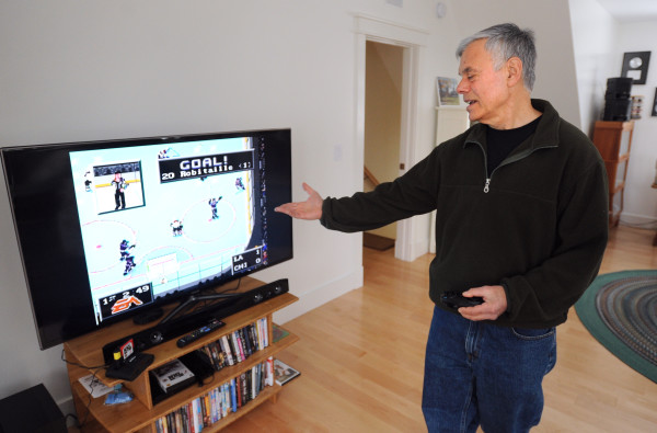 Mark Lesser plays the &quotNHL '94&quot game at his Surry home. Lesser had a long career in video game development, writing the programs for the earliest Mattel handheld games and one of the most popular sports games, &quotNHL '94.&quot