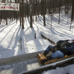 A two-man team finishes a run during the U.S. National Toboggan Championships at the Snow Bowl in Camden on Saturday.