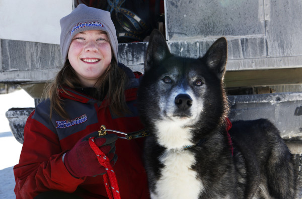 Lara Renner, 12, from Alton, New Hampshire, poses for a portrait with one of her sled dogs, Storm, outside the Lonesome Pine Ski Lodge in Fort Kent Friday. Renner is the youngest musher competing in the Can-Am races this weekend. She is competing in the 30-mile race.