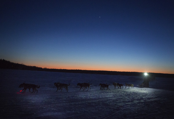 A musher crosses Portage Lake at sunset during the 2015 250-mile Can-Am Crown International dog sled race at the first check point at Portage Lake Saturday.