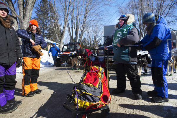 Ashley Patterson (center) gets help from Meg Burden putting on her bib number puts booties on her Alaskan huskies before the start of the 250-mile Can-Am Crown International dog sled race starting in Fort Kent Saturday.