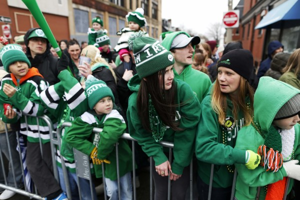 Spectators watch the St. Patrick's Day Parade move down Broadway in South Boston, Massachusetts  March 15, 2015.