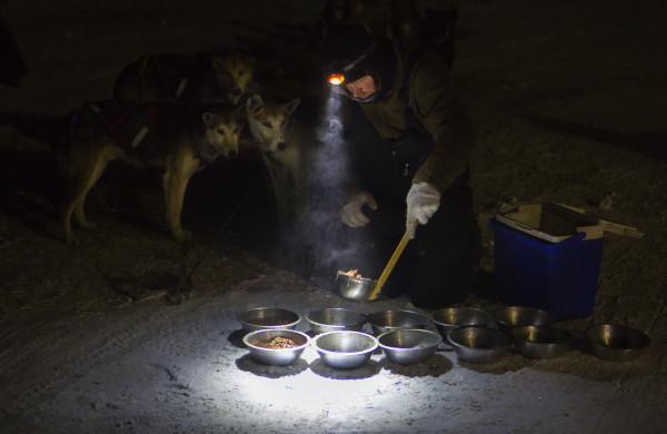 Denis Tremblay makes warm food for his dogs at the second check point of the 250-mile Can-Am Crown International dog sled race at Rocky Brook on Sunday.