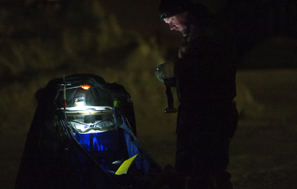Denis Tremblay checks his headlamp during the 2015 250-mile Can-Am Crown International dog sled race at the second check point at Rocky Brook on Sunday.