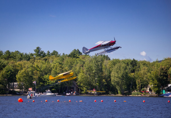Two planes take off in unison during the spot landing competition at the International Seaplane Fly-In on Moosehead Lake in Greenville in September 2014.