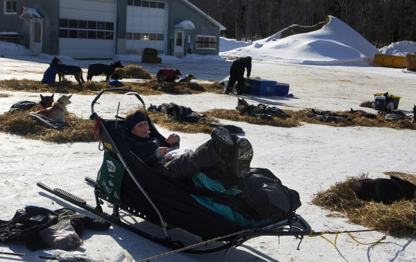 Christine Richardson relaxes in her sled basket at the third check point of the 250-mile Can-Am Crown International dog sled race at Syl-Ver on Sunday.