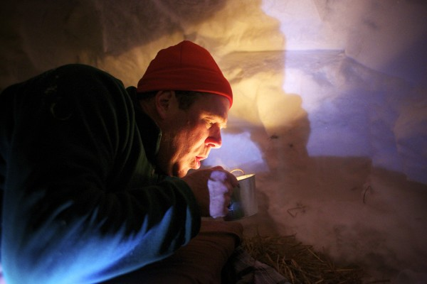 Bangor Daily News Outdoors Editor John Holyoke blows out a candle before sleeping inside a quinzhee, a type of snow shelter, that students at Unity College built as part of a winter ecology class.