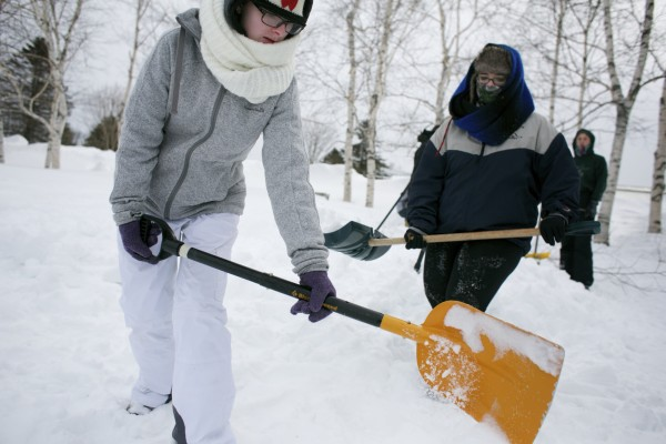 Emelia Waterman (left) and Catherine Bilodeau shovel snow while making a quinzhee, a snow shelter, at Unity College
