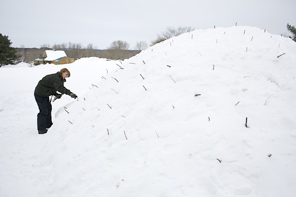Unity College student Elle Gilchrist places sticks in the walls of a quinzhee that her winter ecology class is building to act as guides for digging out the snow shelter Thursday in Unity.