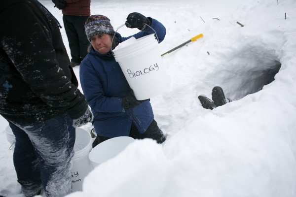 Unity College winter ecology adjunct instructor Dianne Kopec hands off a bucket while removing snow from inside a quinzhee, a type of snow shelter, that her students built as part of their class Thursday.