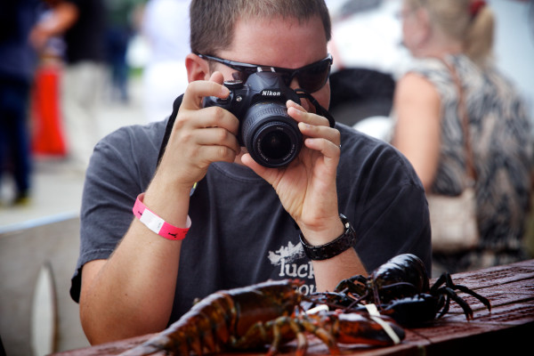 Kevin Klucher of Maryland snaps a photo of a live lobster in Rockland  at the 67th annual Maine Lobster Festival in July 2014.