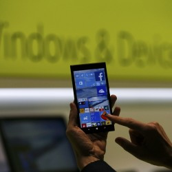 A Microsoft representative shows a smartphone with Windows 10 operating system at the CeBIT trade fair in Hanover, Germany. March 15, 2015. REUTERS/Morris Mac Matzen
