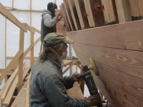 Tom Gerhardt uses a sander on the schooner Nathaniel Bowditch during its restoration.