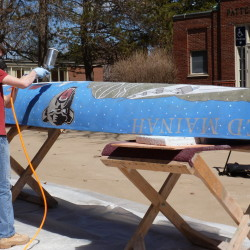 Eric Farnsworth applies a sealant to the concrete canoe he and engineering students at the University of Maine designed and built. The canoe was entered in the New England Regional Concrete Canoe Competition on Friday and Saturday.