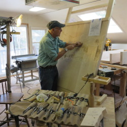 Eddie Harrow, retired pulmonologist and skilled woodcarver, works on a large woodcarving project in his home workshop in Dedham.