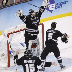 Providence College Friars goalie Jon Gillies (32) celebrates with defenseman Kyle McKenzie (5) and forward Steven McParland (15) after defeating the Boston University Terriers 4-3 in the championship game of the Frozen Four college ice hockey tournament Saturday night at the TD Garden in Boston.
