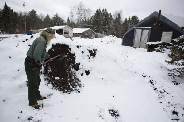 Tom Roberts, owner of Snakeroot Organic Farm in Pittsfield, hoes down his compost pile to show how frozen it is.
