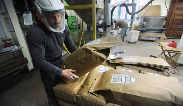 Cory Trial, a miller at the Maine Grains grist mill, stacks bags of organic rye flour while working at the Skowhegan facility.